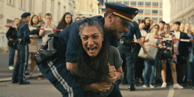 Polizist hält am Tatort schreiende Mutter fest, die weiß, dass ihr Sohn während des Anschlages im Shopping Center war.