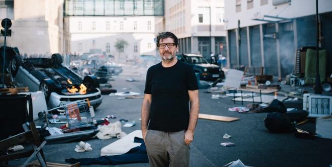 David Schalko steht in einer Straße voller Trümmer und umgestürzter, zum Teil brennender Autos